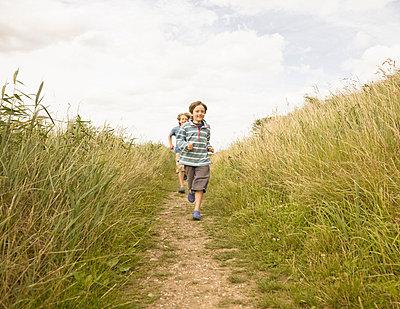Boys running down path - p4297218f by Ashley Jouhar
