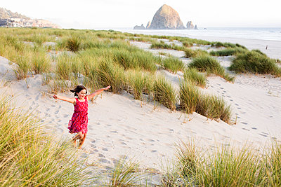 Caucasian girl running with arms outstretched on beach - p555m1411258 by Adam Hester