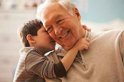 Caucasian boy telling grandfather a secret - p555m1478093 by KidStock