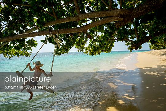 Boy swinging on beach