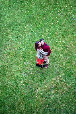 Junges Paar umarmt sich auf einer Rasenfläche - p1248m2141926 von miguel sobreira