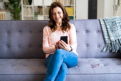 Smiling mature woman using mobile phone while sitting on sofa at home - p300m2266122 by Giorgio Fochesato