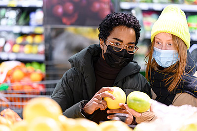 Female friends buying fruits in supermarket during COVID-19 - p300m2282881 by Katharina und Ekaterina