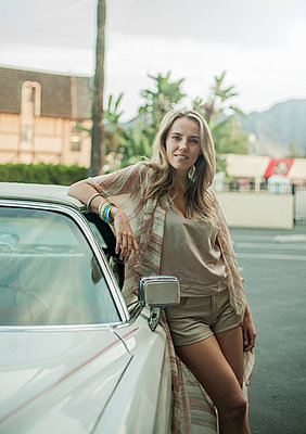 Portrait of young woman, leaning against car, smiling - p429m1547842 by Seb Oliver
