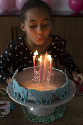 Girl blowing out candles on birthday cake - p623m1086442f by Anne-Sophie Bost
