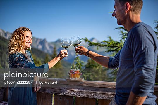 Junges Paar beim Anstoßen mit Wein - p1007m2222287 von Tilby Vattard
