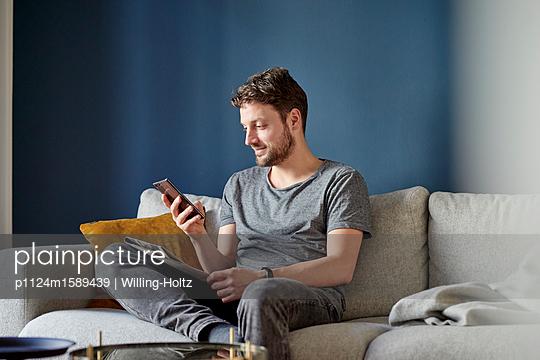 Junger Mann liest eine SMS - p1124m1589439 von Willing-Holtz