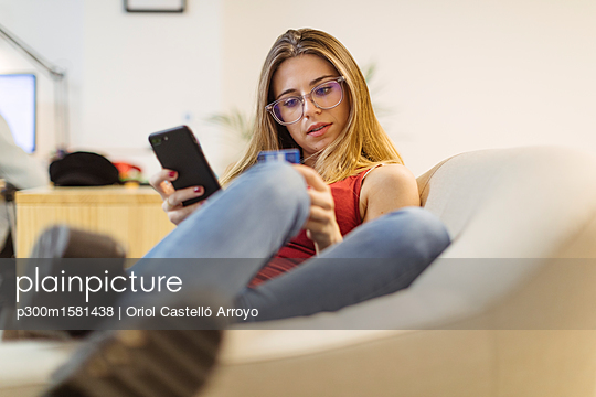 Young woman using smartphone and credit card in the office - p300m1581438 von Oriol Castelló Arroyo