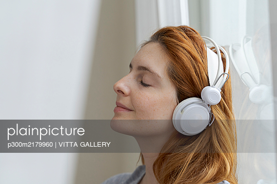 Young woman listening to music with headphones at the window - p300m2179960 by VITTA GALLERY