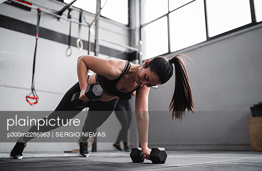 Smiling woman exercising with dumbbells in gym - p300m2286963 by SERGIO NIEVAS