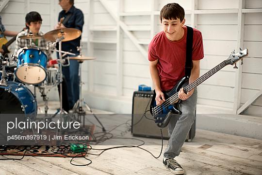 Teenage boy playing a bass guitar enthusiastically. - p456m897919 by Jim Erickson