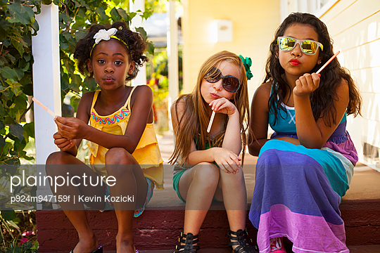 Three girls pulling faces on porch - p924m947159f by Kevin Kozicki