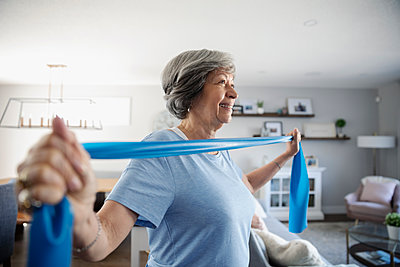 Smiling senior woman exercising with resistance band in living room - p1192m2109854 by Hero Images