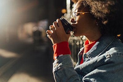 Close-up of young woman with eyes closed drinking coffee while standing outdoors - p300m2213903 by Boy photography