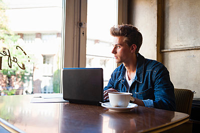 Young male student sitting at cafe table using laptop and gazing out of window - p429m983384f by Daniel Ingold