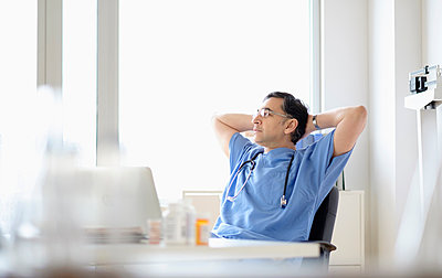 Mixed race doctor relaxing at desk - p555m1305615 by JGI/Tom Grill