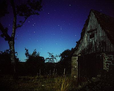 Verlassener Schuppen unter einem Sternenhimmel - p945m1196291 von aurelia frey