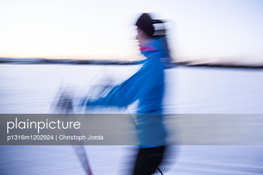 Young woman cross-country skiing at sunset, Allgaeu, Bavaria, Germany