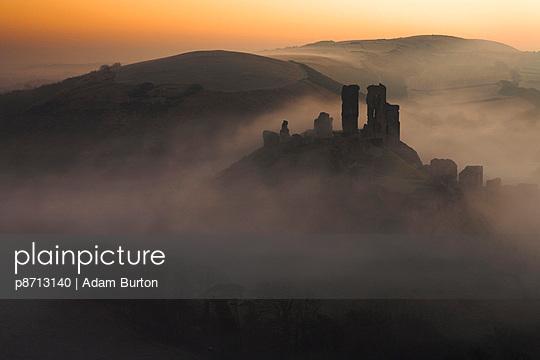 A sea of mist swirls around the base of Corfe Castle at dawn, Corfe, Dorset, England, United Kingdom, Europe - p8713140 by Adam Burton