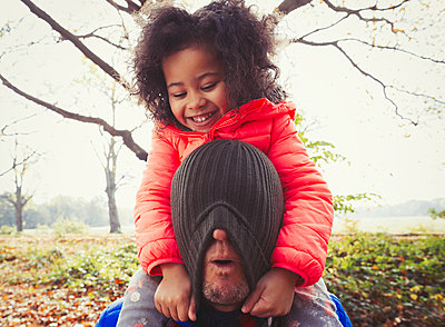 Playful daughter pulling stocking cap over fathers face in autumn park - p1023m1402944 by Paul Bradbury
