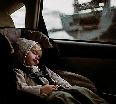 Toddler sleeping in carseat in back of car - p1166m2095988 by Cavan Images