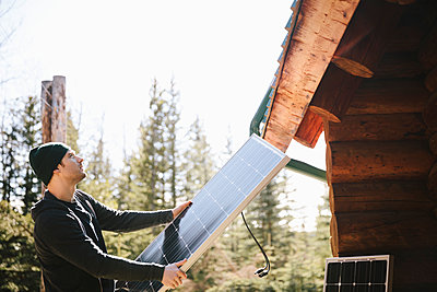 Man installing solar panels outside cabin - p1192m2093977 by Hero Images