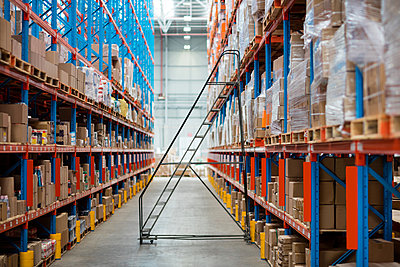 Front view of empty aisle in warehouse  - p1315m1147780 by Wavebreak