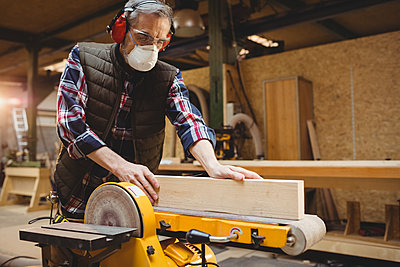 Carpenter sawing a plank of wood - p1315m1167722 by Wavebreak