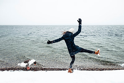 Grey goose and young woman at Lake Starnberg in winter - p300m2084007 by Wilfried Feder