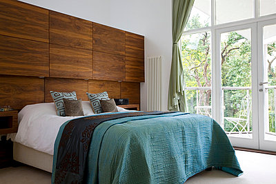 Turquoise bedspread with oversized wooden headboard in Cambridgeshire home  UK - p3493441 by Robert Sanderson