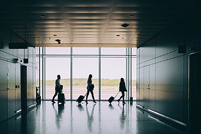 Side view of silhouette business colleagues pulling luggage while walking in corridor at airport - p426m2074776 by Maskot