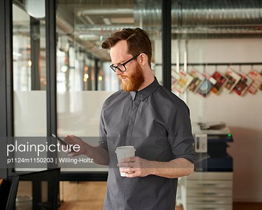 Mann mit Smartphone und Coffee to go im Büro - p1124m1150203 von Willing-Holtz