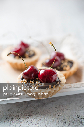 Close-up of tart with chocolate and cherries served in plate on table - p300m2144249 by Mandy Reschke