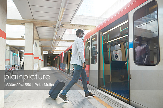 Male entrepreneur business travel boarding metro train at station during pandemic - p300m2241550 by Pete Muller