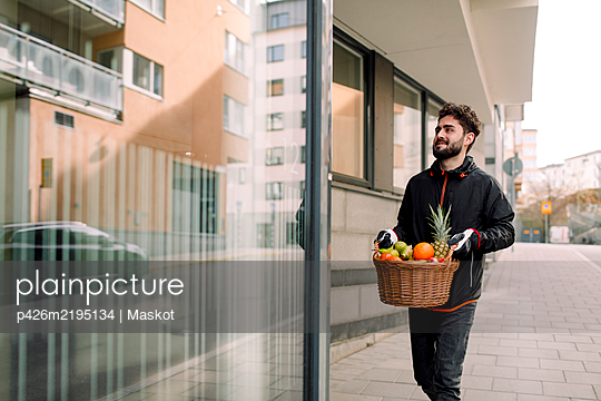 Young man delivering fruit basket in building - p426m2195134 by Maskot