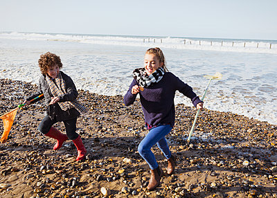 Brother and sister with nets running from ocean onto beach - p1023m1106087f by Sam Edwards