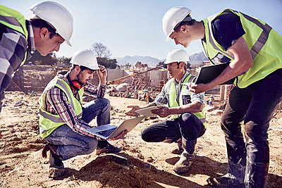 Construction workers and engineers using digital tablets at sunny construction site - p1023m1402909 by Trevor Adeline