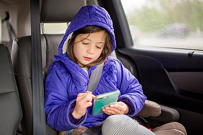 A small child wits in her carseat on a trip playing with a cell phone - p1166m2165930 by Cavan Images