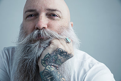 Close up portrait confident Caucasian male hipster with gray beard and tattooed hand on chin - p1192m1213126 by Hero Images
