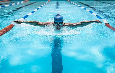 Young Caucasian male swimmer swimming butterfly stroke in swimming pool - p1315m2091034 by Wavebreak