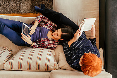 Adult daughter using tablet and mother reading book at home - p300m1356560 by Zeljko Dangubic
