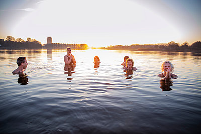 Smiling women meditating while having fun with male friends in water - p300m2293459 by Frank van Delft