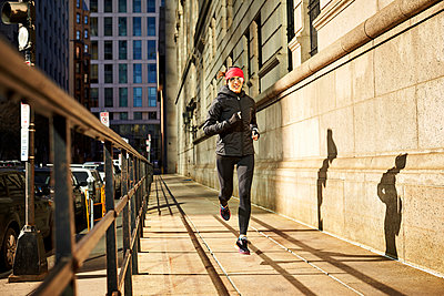 Woman jogging in city - p343m2046928 by Josh Campbell