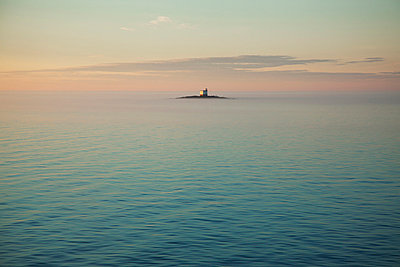 Lighthouse on small island on open sea - p528m713851 by Kenneth Hellman