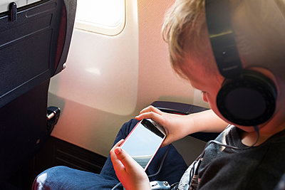 Little boy listens to music on smartphone - p890m1467369 by Mielek