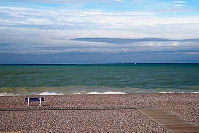 Empty bench on shingle beach - p924m806960f by Still Factory