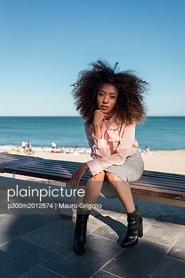 Portrait of beautiful young woman with afro hairdo sitting on a bench at the beach - p300m2012874 by Mauro Grigollo