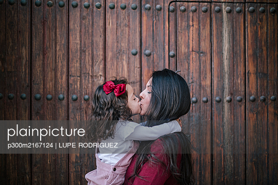 Mother holding and kissing little daughter outdoors - p300m2167124 by LUPE RODRIGUEZ