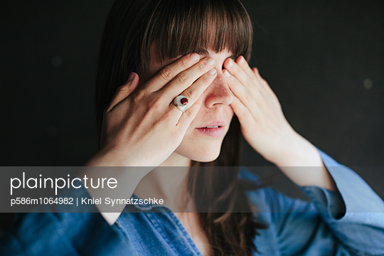 Woman with hands covering eyes - p586m1064982 by Kniel Synnatzschke