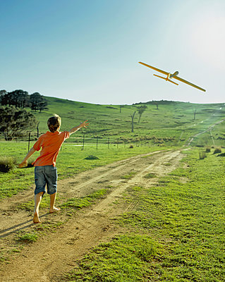 Boy throwing glider - p1125m943659 by jonlove